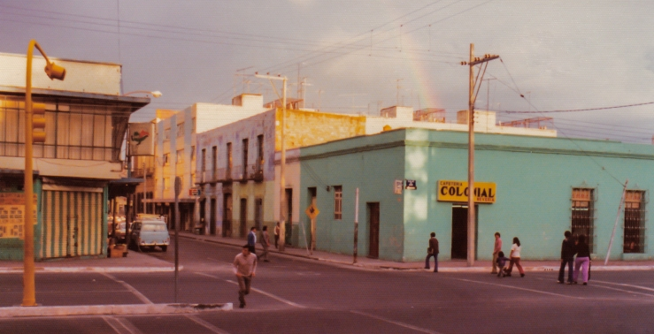 1975.06.01.03 Puebla A rainbow adds more color to an inner-city scene in Puebla, Mexico.